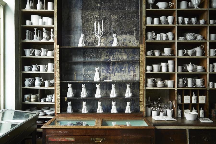 エイジングを重ねた什器に白い陶器がぎっしり並ぶ。窓から入る自然光による陰影で奥行きのある空間に。photo : Stephen Johnson