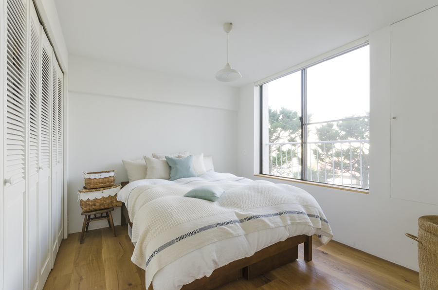 ベッドルームには大きな収納を作り、ベッド以外の家具は置かないようにした。小物類は籐のバスケットに。