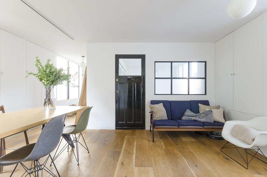 真っ白な空間に黒のアンティークのドアが奥行きを与える。幅広の床材の効果なのか、広さと落ち着きが感じられる。