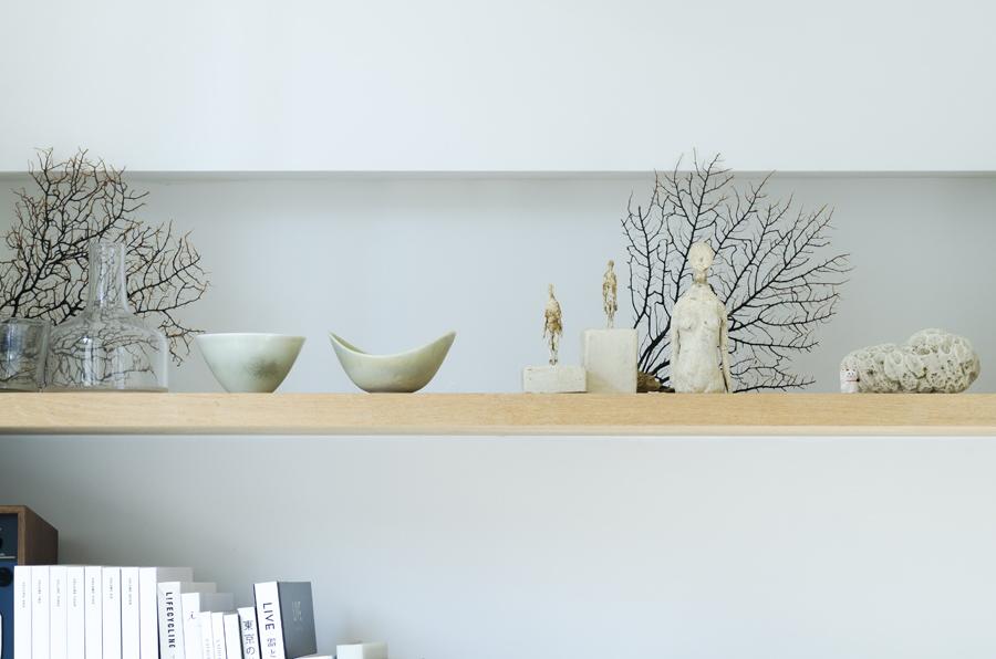 サンルームの棚の上。アーティストの作品やタイの雑貨、サンゴなどが調和している。