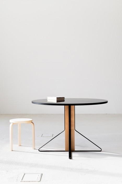 翼型のスチールレッグが四方に広がる丸テーブル。3本脚のスツールが控えめに主張。