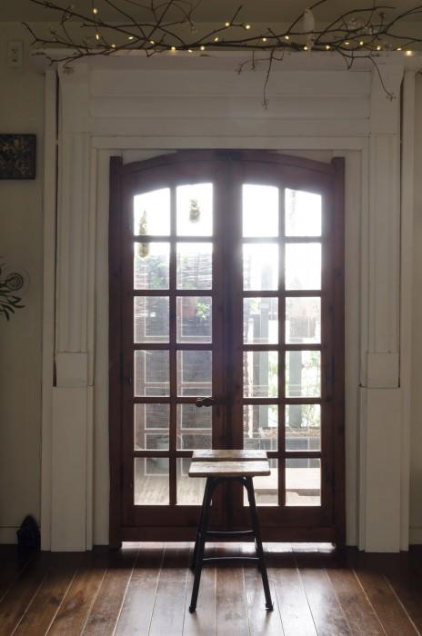 マントルピースを窓枠にあしらい格子窓を取り付けた。標本用ガラススタンドにコケを入れて飾りに。スツールはフランスの美術学校で使われていたもの。