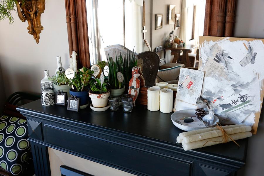 暖炉の上のキャンドルや多肉植物。右のボードは、ハロウィンパーティで柩を作った時の箱の一片だそう。