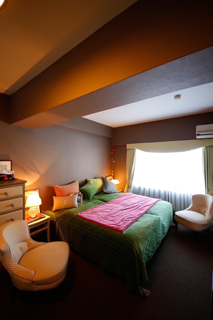 ベッドカバーとクッションの色使いで部屋のムードを作っている。イスの丸みのあるフォルムも素敵。