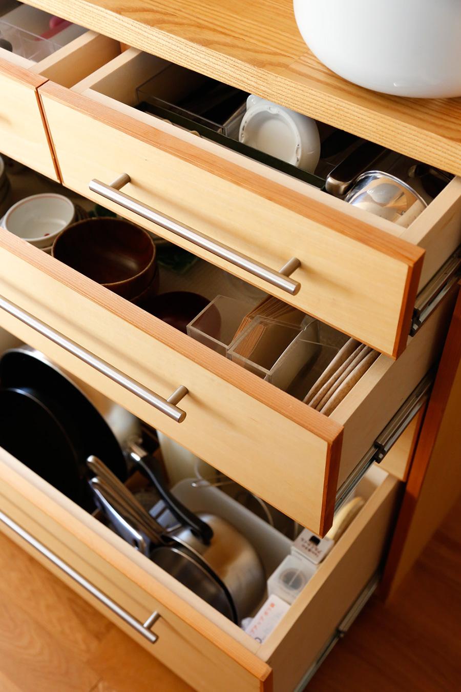 ダイニングテーブルに近い位置には、お箸やフォークなどを収納。下段のフライパンや鍋は、縦に入れることで取り出しやすくしている。