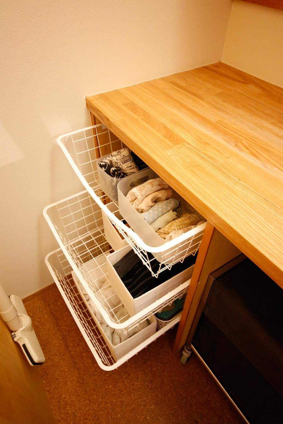 洗面所の中のデッドスペースには、引き出しのバスケットを使用。着替えなどバスまわりのものを収納している。