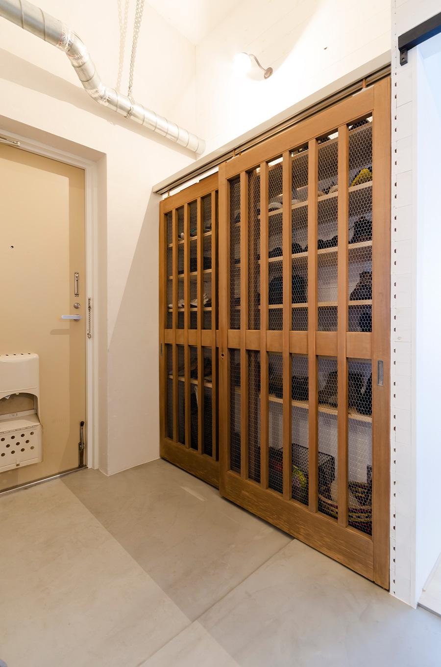 古い門扉に網を使って靴箱をDIY。壁はフローリングの板にペンキを塗った。