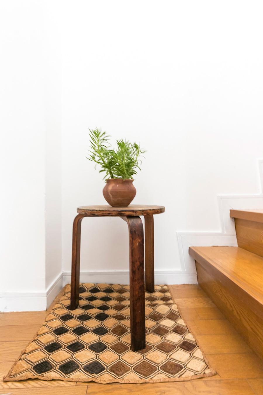 階段の踊り場には、アアルトの三脚スツールの上に小さなグリーンをひとつ。