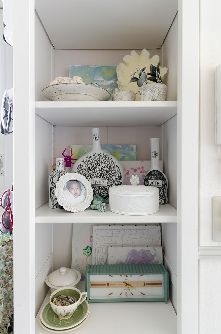 スージー・クーパーのコーヒーカップや、子どもの思い出の品など。白をベースに飾り付け。