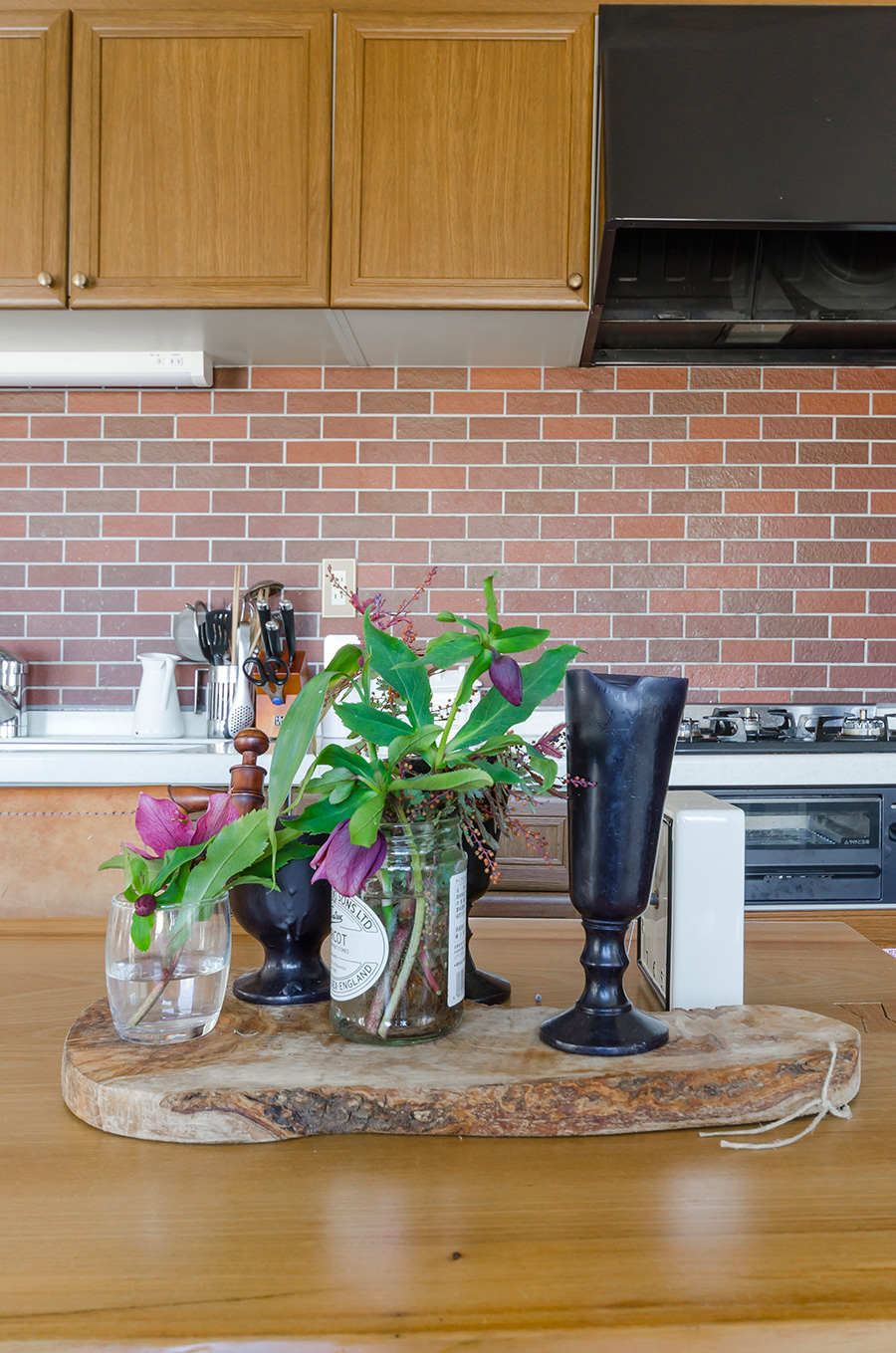 キッチンのテーブルの上にも花をディスプレイ。空き瓶を活用して無造作に。