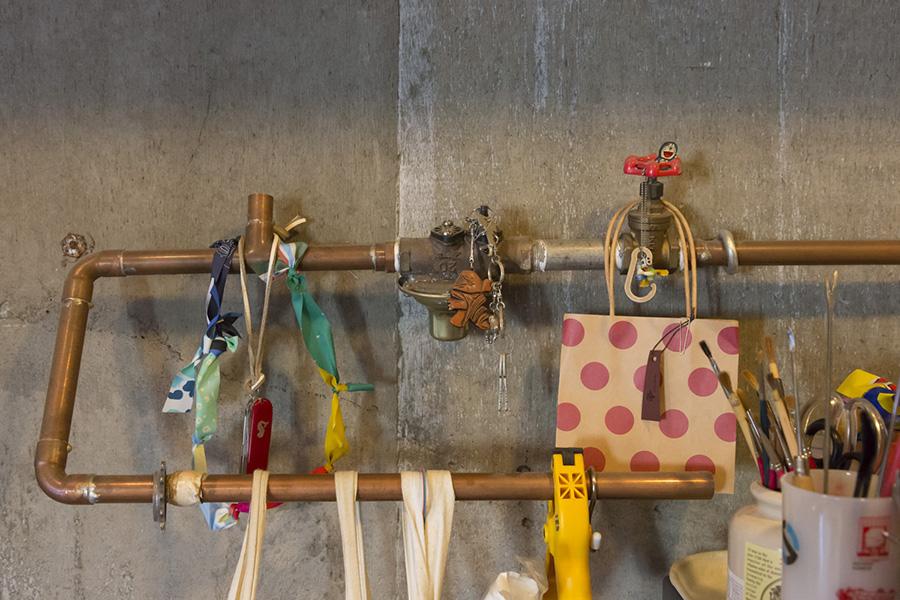 部屋を解体していた時に出た廃材の銅管に道具を吊るす。銅管の色がいい雰囲気。