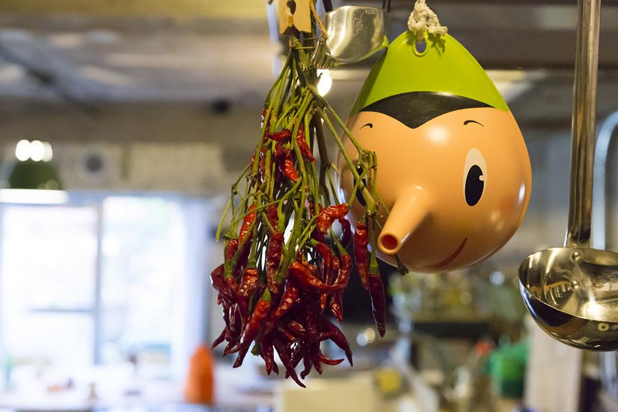 キッチンの道具は吊るして収納。トウガラシと、アレッシィのじょうご「Pino」。
