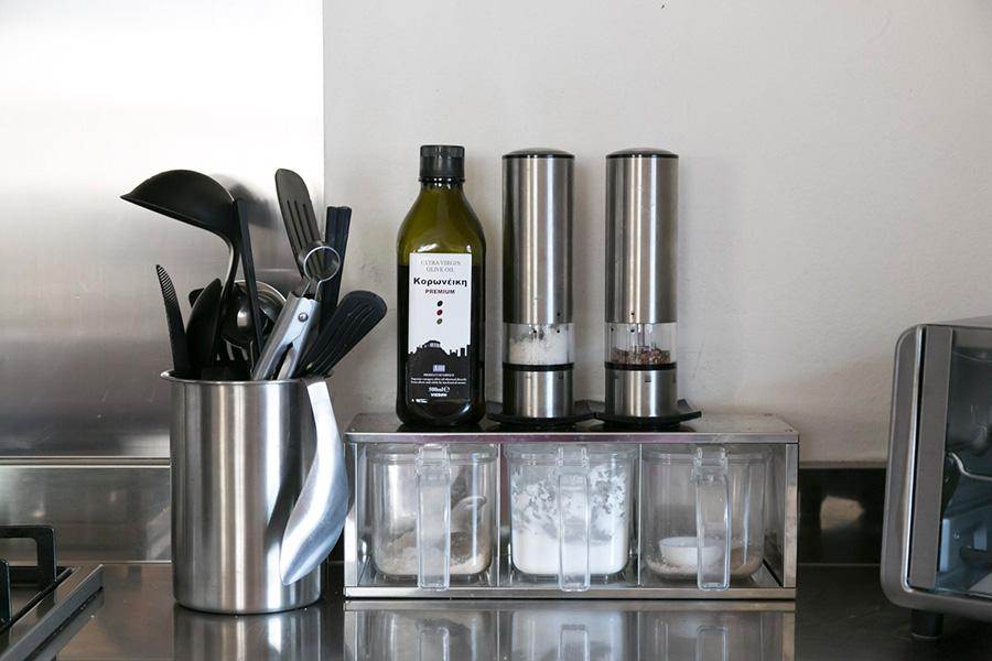 使用頻度の高い調理器具や調味料は、ガス台の横に。シルバーや透明のケースで色調を揃えている。