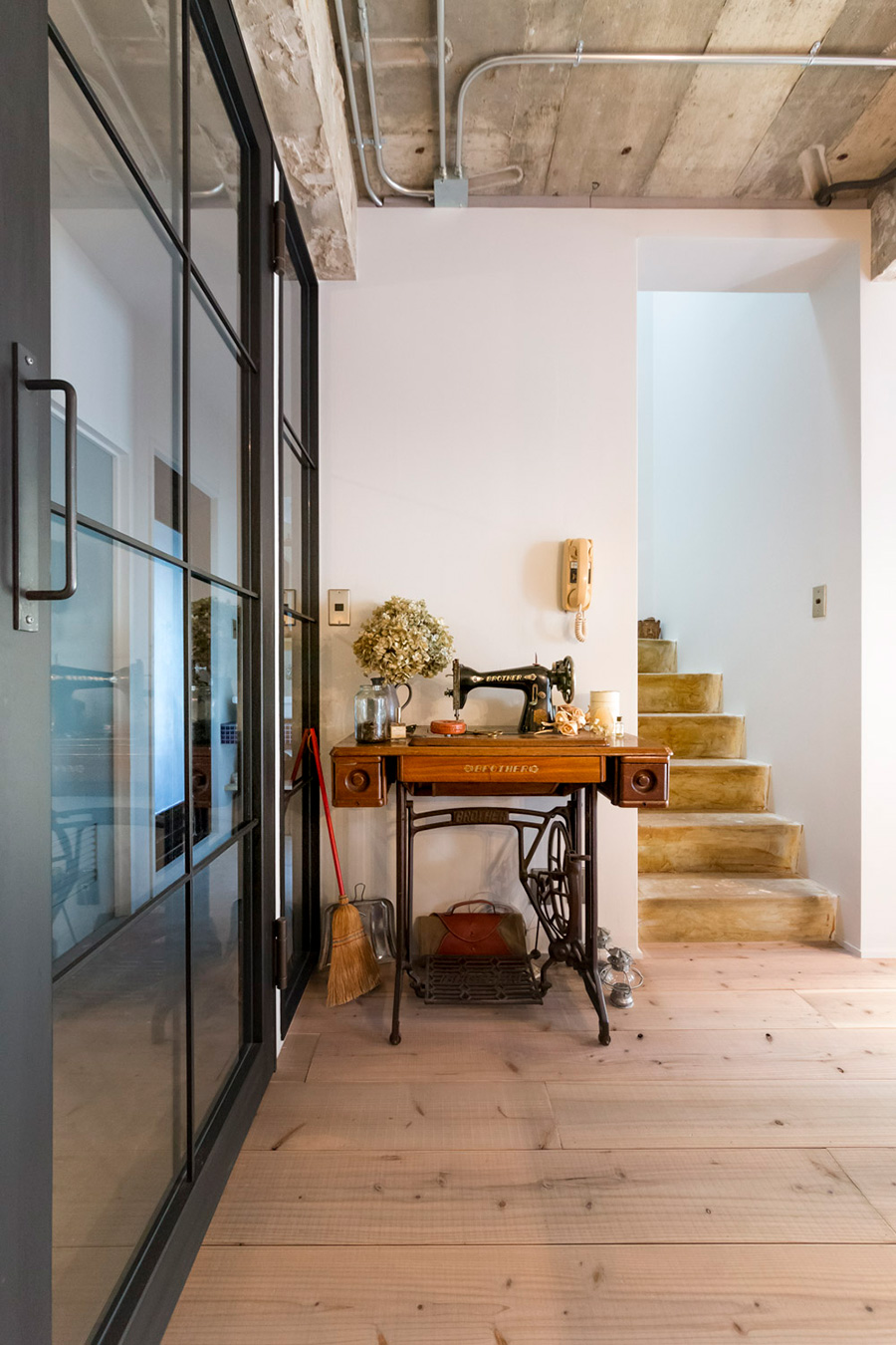 森澤宅のインテリアの雰囲気を決めているのが、古いミシンと、玄関とリビングを仕切るガラスのドアだ。