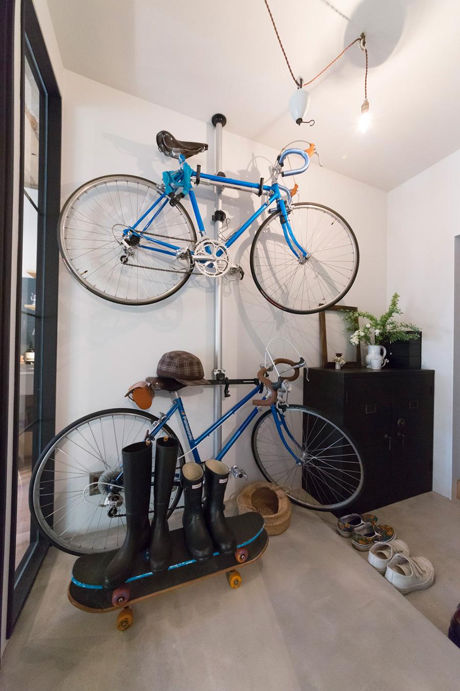 モルタルで仕上げた玄関スペースに自転車を収納。黒いアンティークの金庫を下駄箱として使っている。