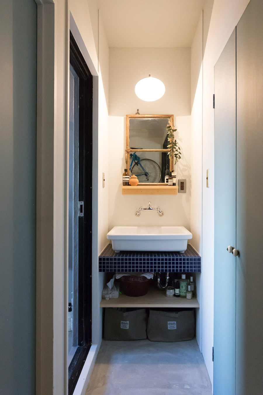 廊下の突き当りが洗面スペース。実験用のシンクを、ブルーのタイルに置くように設置。レトロな蛇口もキュート。