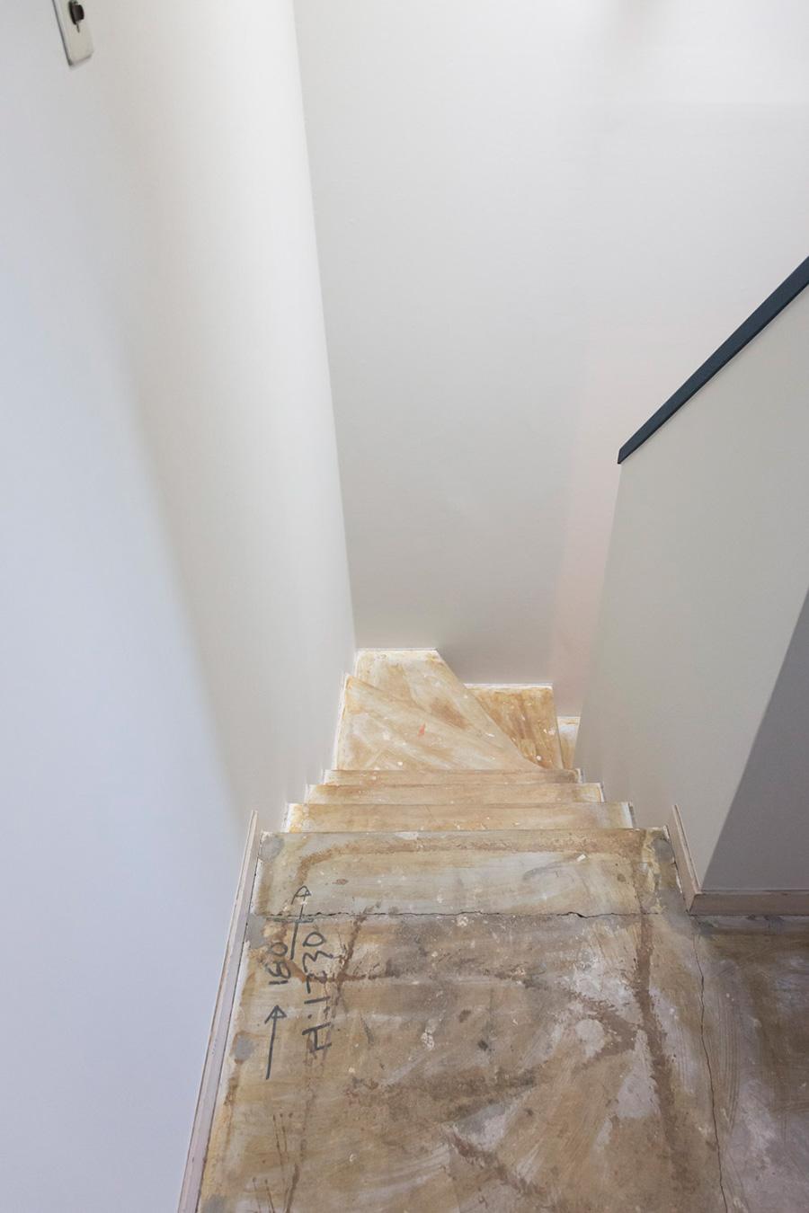 階段の床もカーペットを剥がし、そのまま床材を貼らずに仕上げた。建物を建てた際の大工さんのメモがそのまま残る。