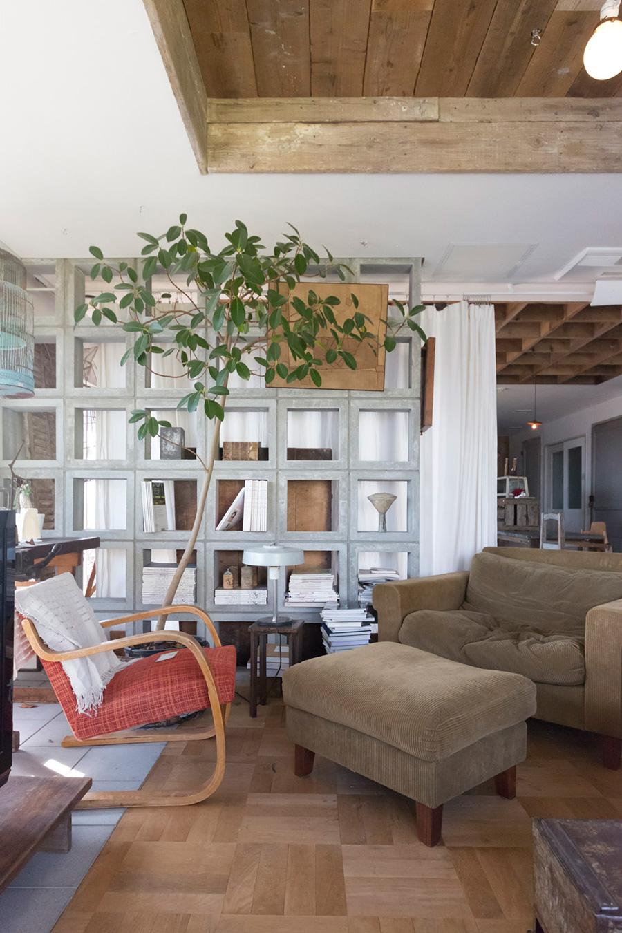 正方形のコンクリートブロックと白いカーテンで、ゆるやかにリビングの空間を分けている。