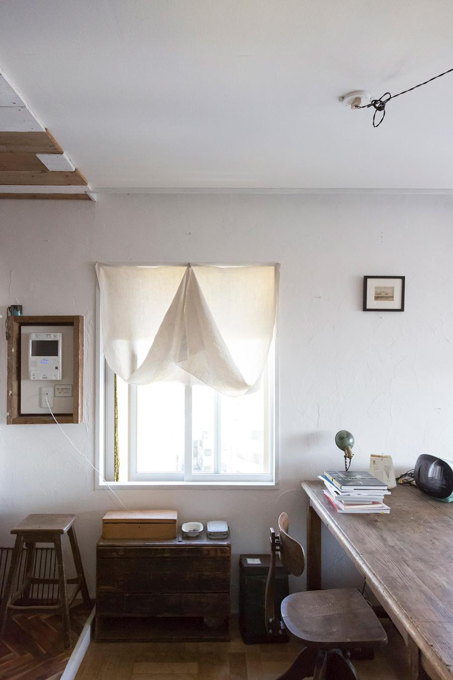 サッシの内側は色を白に塗り替えた。白いカーテンの裾の一箇所を上に留めて、表情のある窓を作る。