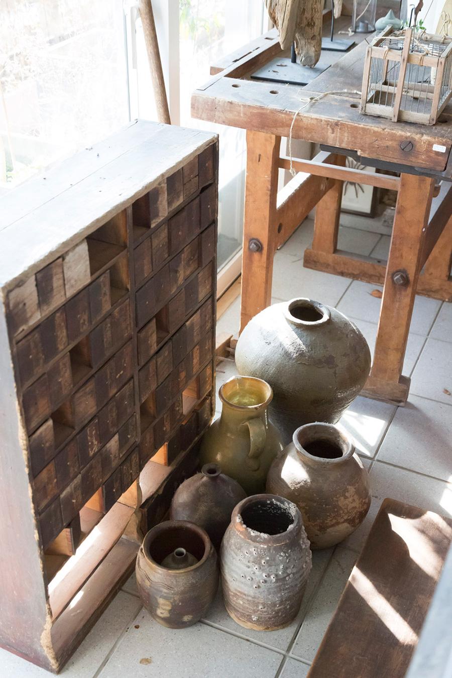窓際の床にはタイル貼りの場所も。アンティークの引き出しの前に、様々な形の壺を並べる。