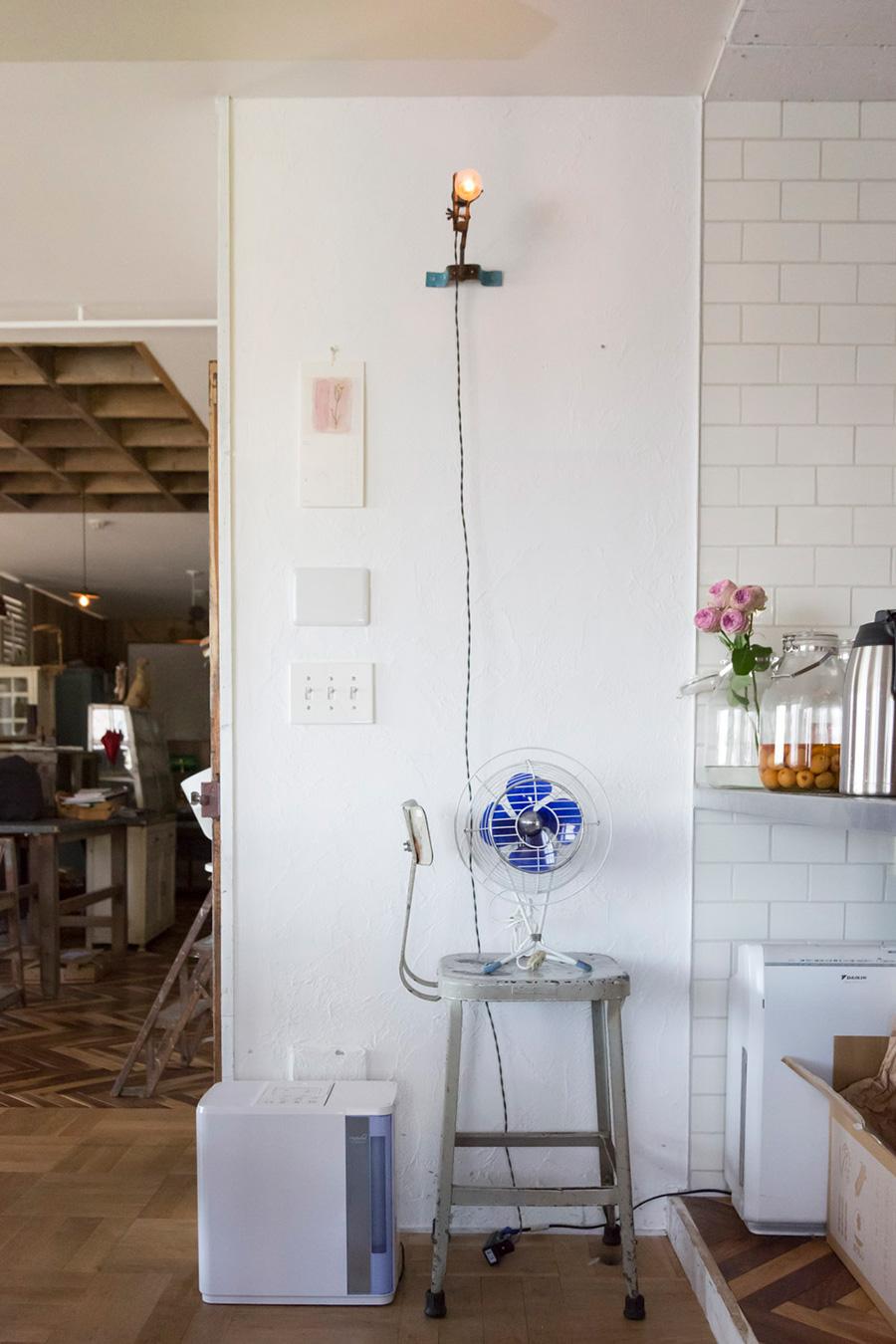 アンティークの万力で電球を挟んだだけのライト。ブルー✕白の家電が、白の漆喰の壁の前に収まる。