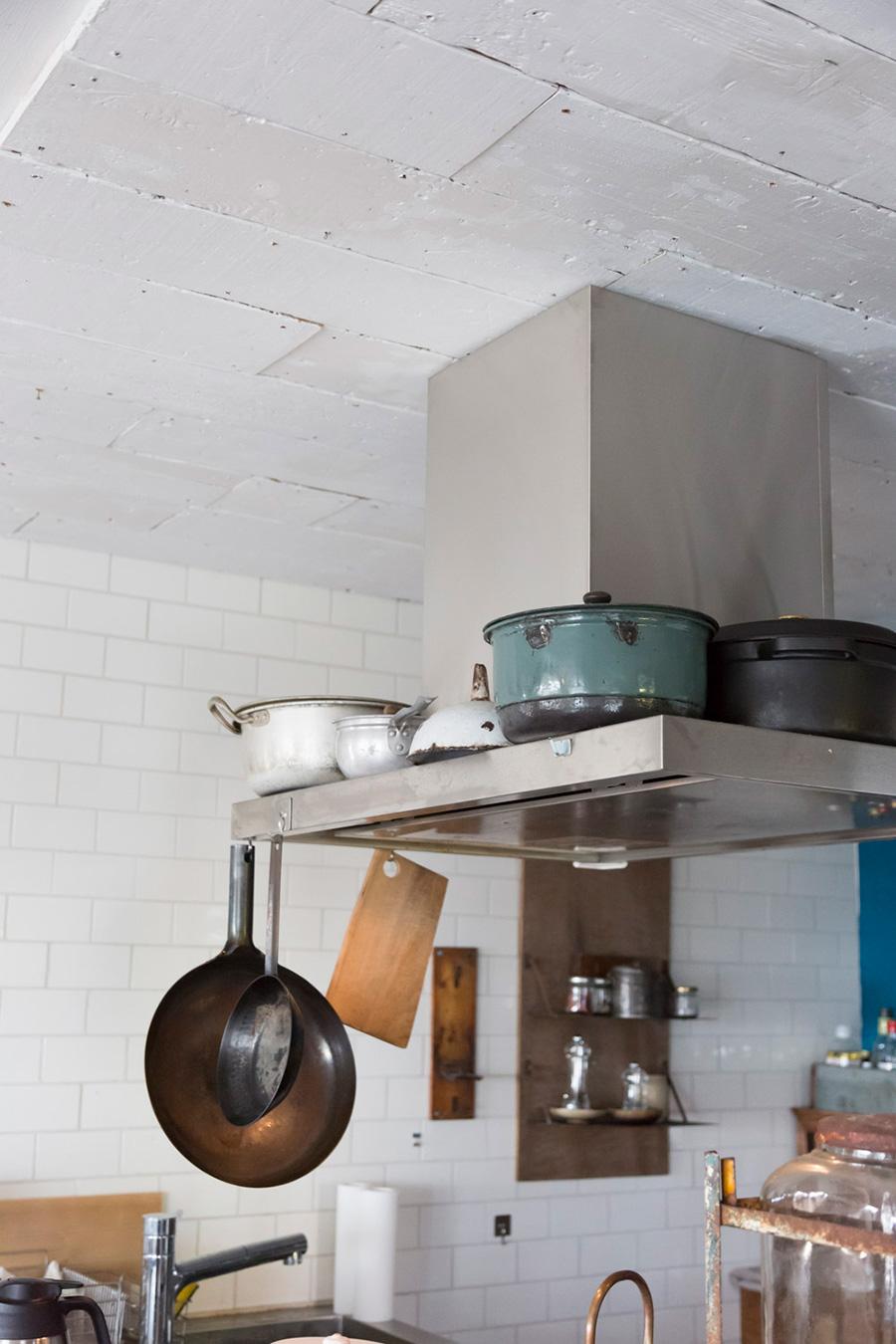 換気扇の周りにアンティークの鍋を置く。天井には白くペイントした板を貼っている。