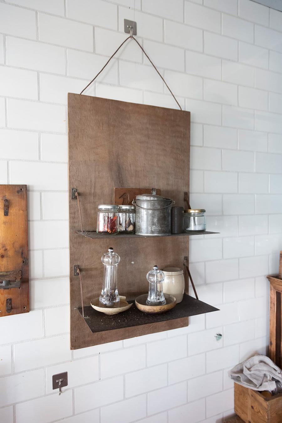 よく使う調味料を並べた吊り棚。塩と胡椒のアクリル製のミルの下にアンティークの皿を敷いている。