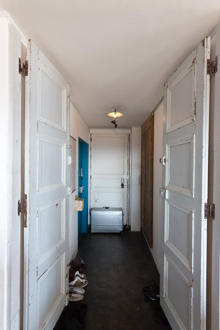 玄関ホールには、たくさんのアンティークの扉。吊り戸の奥は物入れになっている。