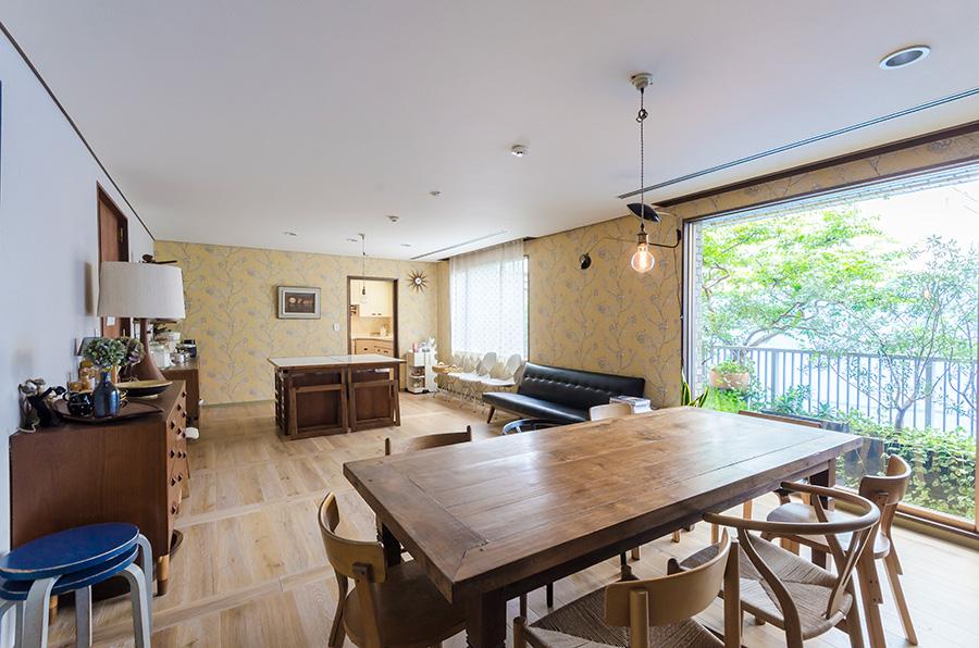 窓の外にはベランダガーデニングや、1階の庭の緑が眺められる。天井が高く落ち着く室内。