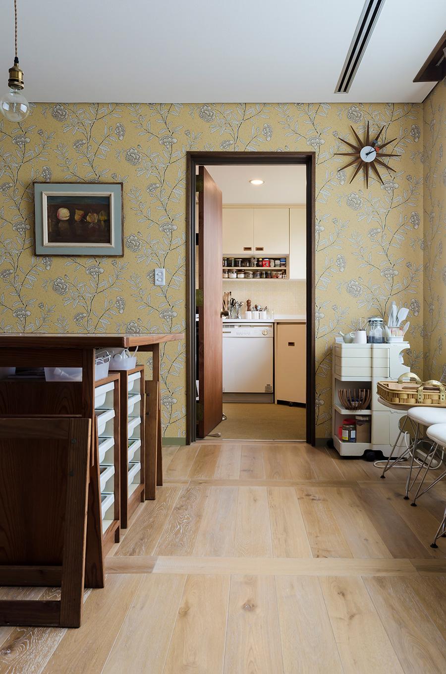 ドアの奥のキッチンも、イエローがテーマ。壁紙に合わせてアートもセレクト。