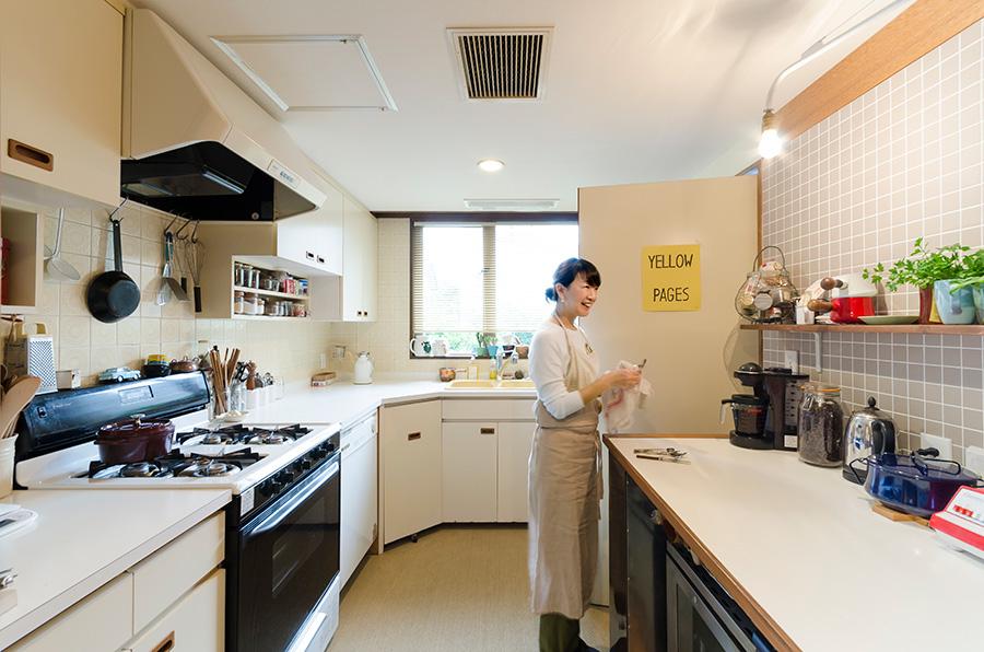 広々とした明るいキッチンはどこか外国風。右側のみ造りつけの収納を取り、水はねOKのタイルを貼った。