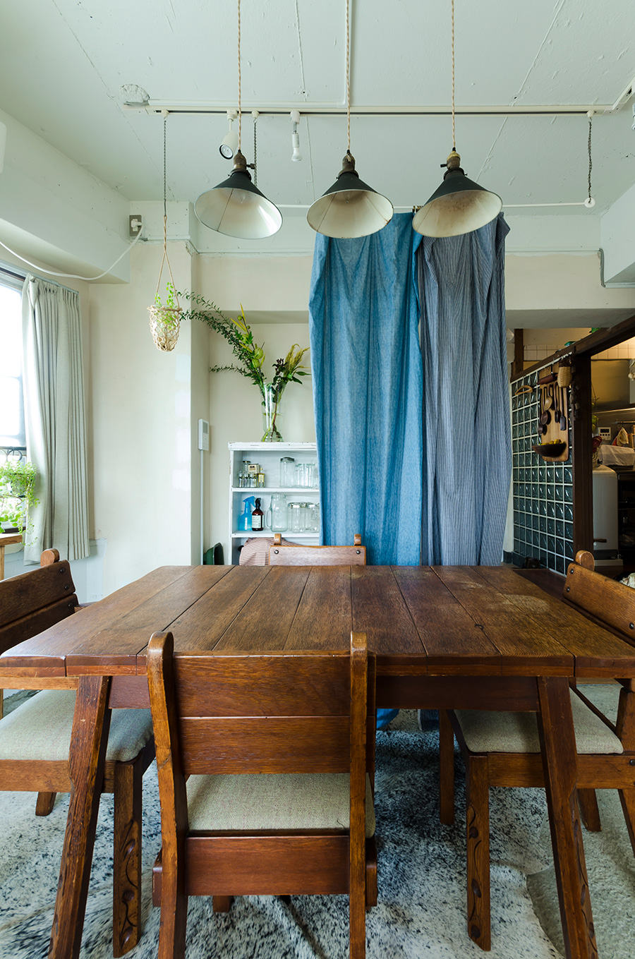手作り感が気に入っているアメリカのアンティークの椅子とテーブルは、ほどよく装飾のあるミッション様式。カーテンをパーテーション代わりに。