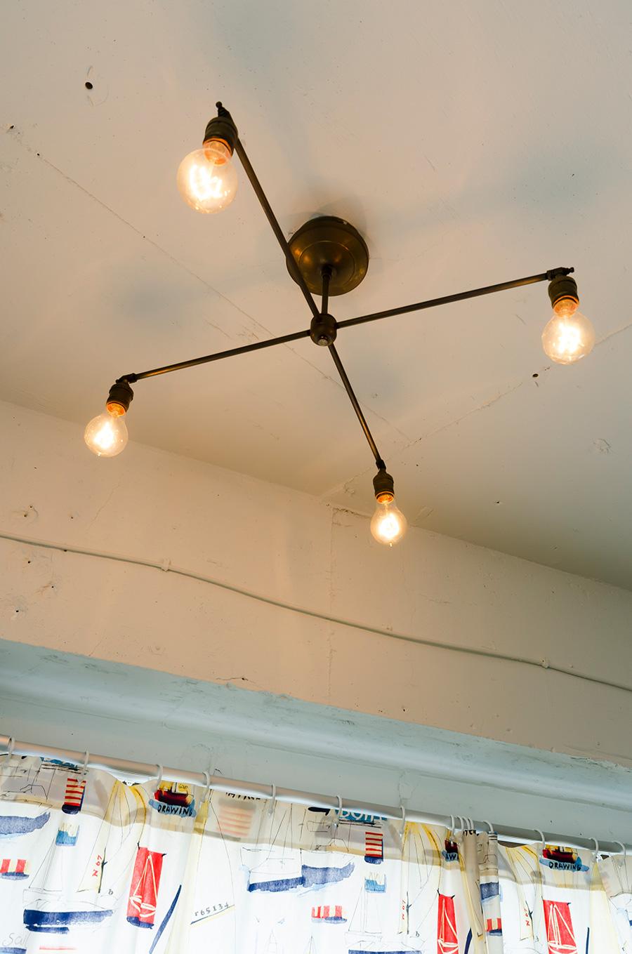 真鍮を使った照明は、杉村さんのデザイン。やわらかい明かりが古い家具を照らし出す。