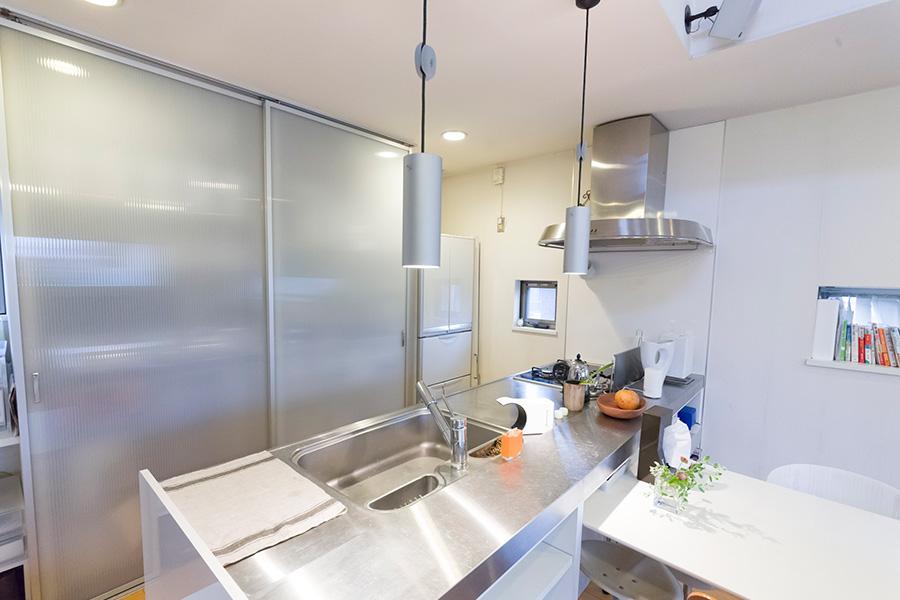 もともと持っていたスチールシェルフを設置するために設けたという棚。現在はDIYで可動棚を設置し、使わないときは扉で隠している。キッチン台のすぐ後ろ側なので、振り返るだけですぐに手が届く。