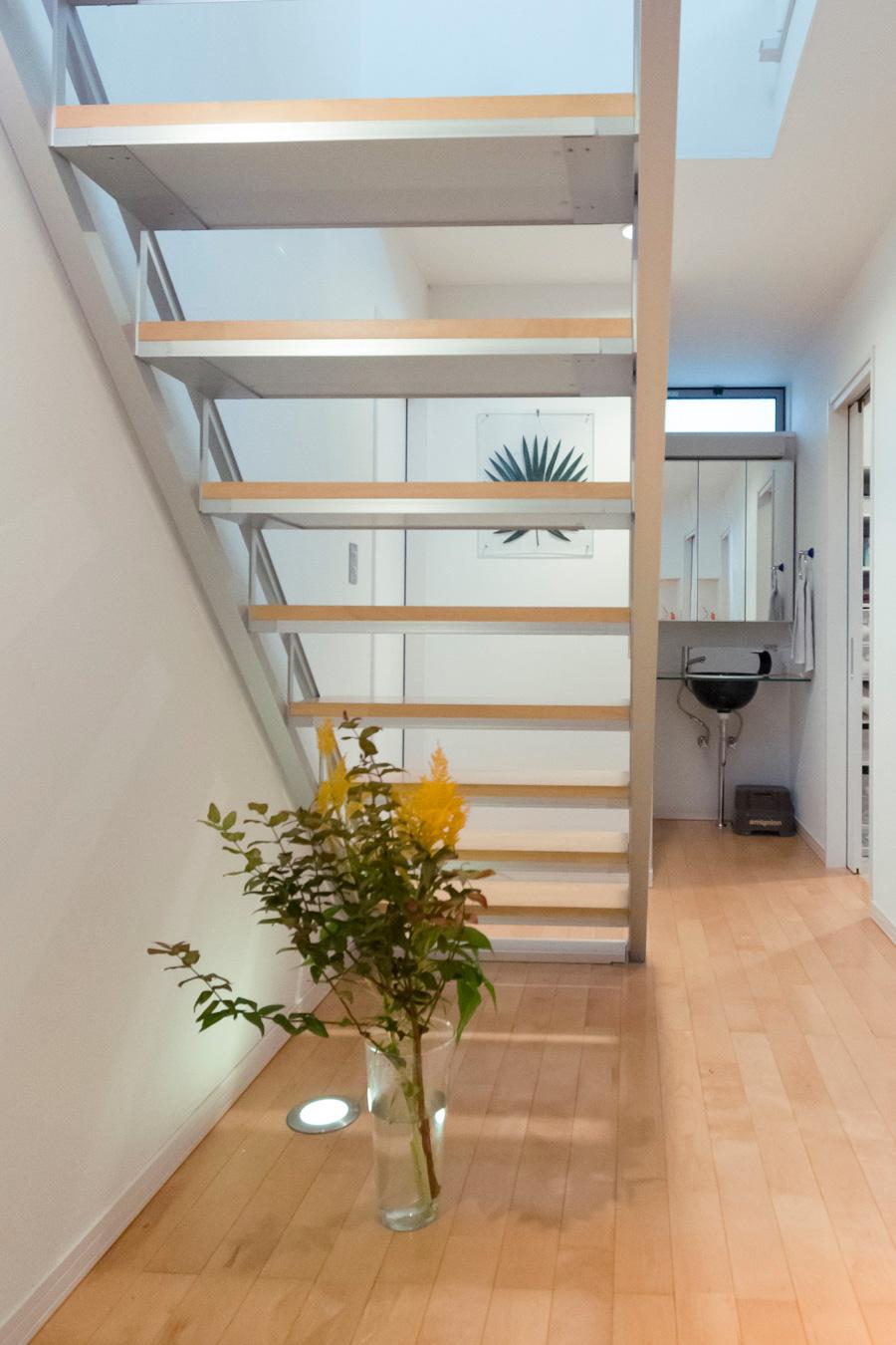 玄関はお客様を花で迎えられるよう、階段をわざと回り込んであがる位置に取り付けたそう。