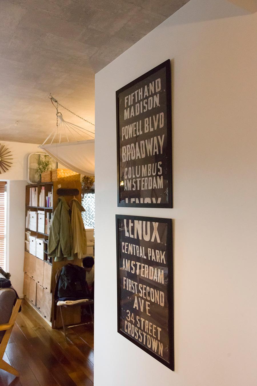 壁にかかっているサインアートは、海外のバスの表示板。「そのままだとつまらなかったので、2つに分けて額装しました」奥が扉を自分でつけた本棚。