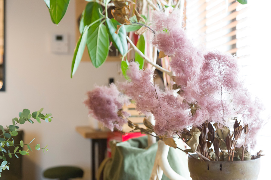 ドライフラワー、切り花、鉢物を、センス良くコーディネイトしている。鉢物のカバーにミリタリーアイテムのバッグを被せるアイディアもおもしろい。