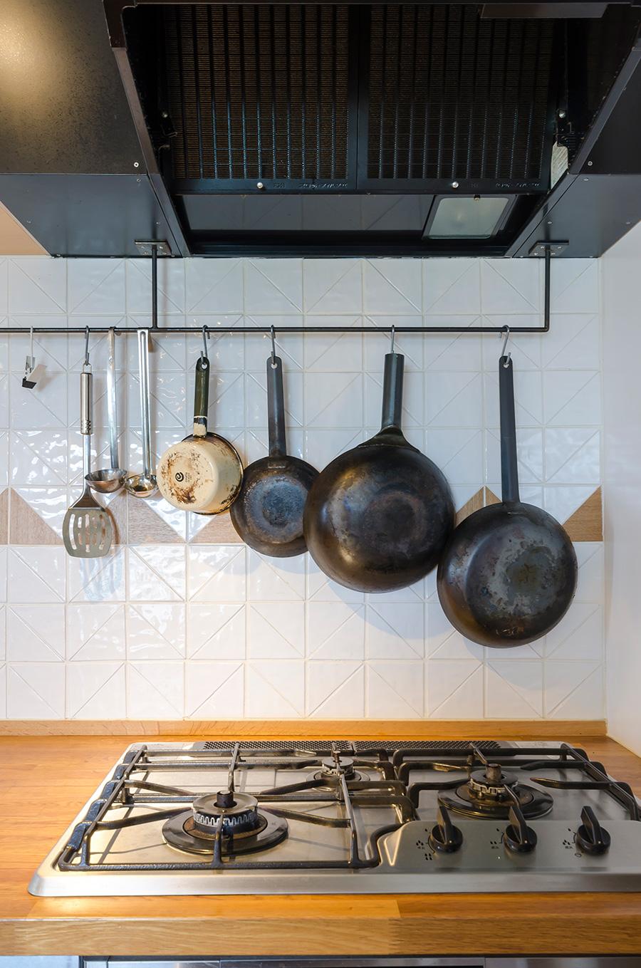 愛用のフライパンや鍋は、パイプに吊り下げて使いやすく。