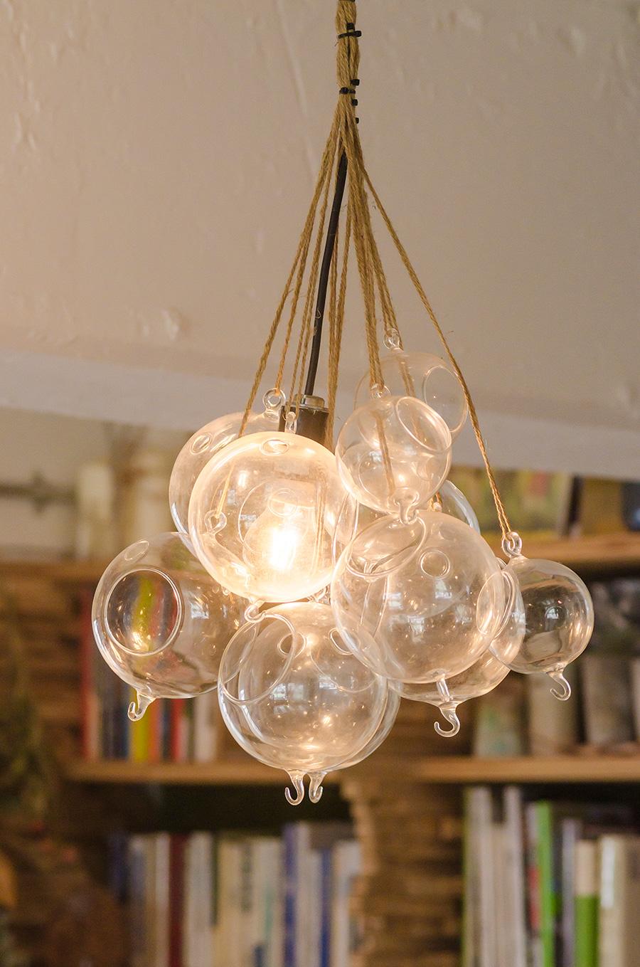 素敵な照明はYさんの手づくり。エアプランツやハンギングプランツ用のガラス容器をたくさん吊るして、真ん中に電球を入れた。