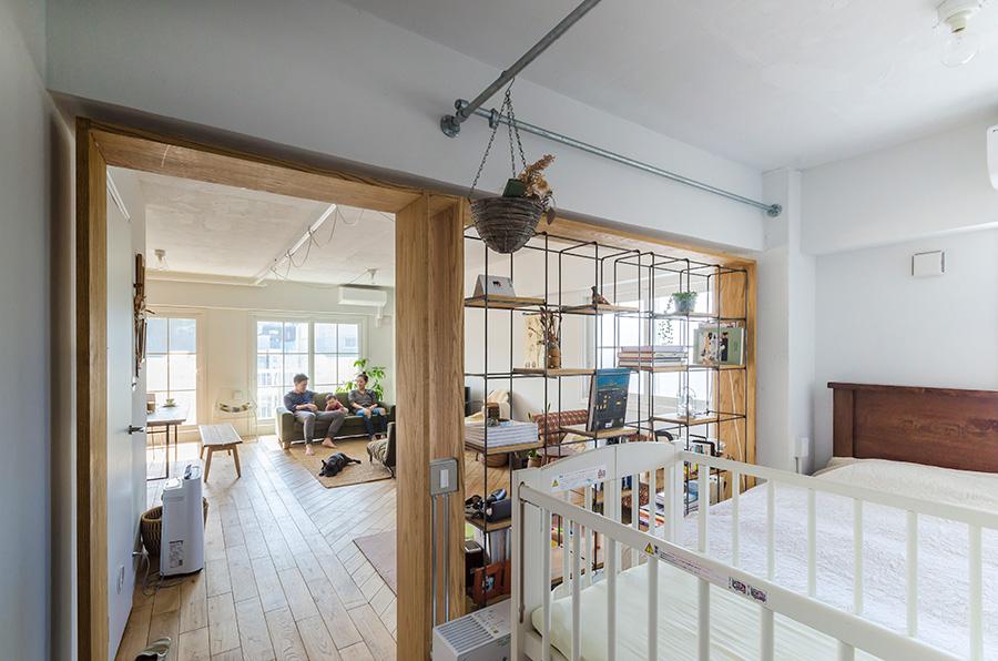 ベッドルームとリビングの間の本棚が、空間をゆるやかに仕切る。