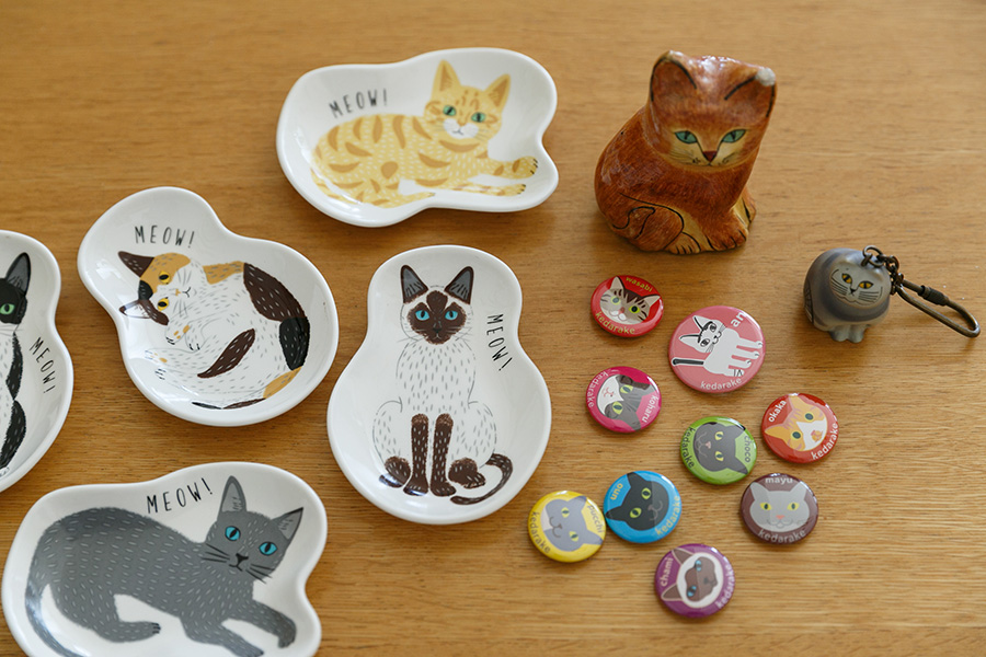 自宅には猫グッズもたくさん。右の缶バッジは、陽子さんが友人のイラストレーターと一緒につくったオリジナルグッズ。売り上げを猫の保護活動にあてている。