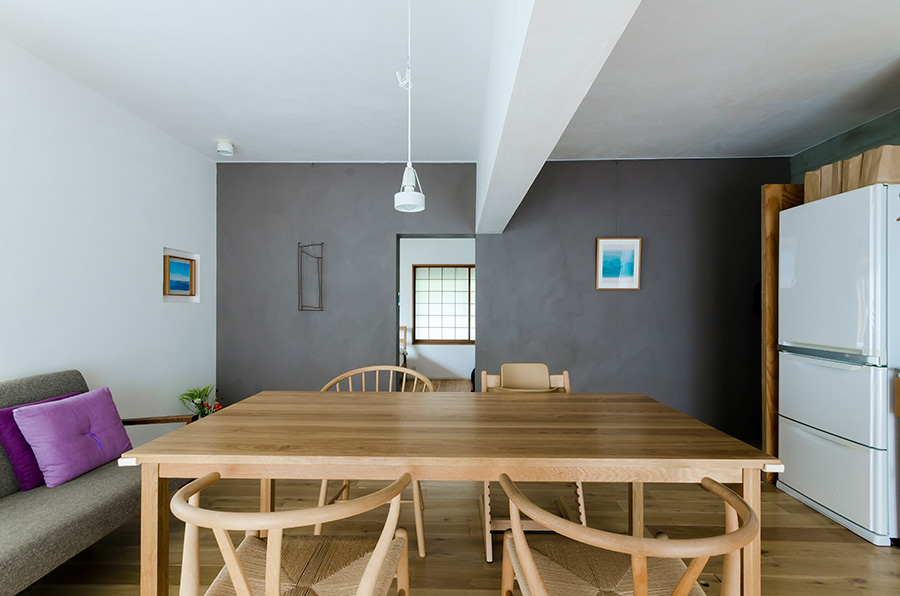 天井の梁を活かし、直線が交差するようなデザインに。グレーの壁の向こうの寝室はダイニングと同じ白にし、空間が層のように重なるよう演出。