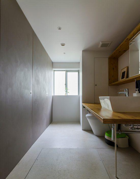 仕切りのない洗面は、北側の窓から光が差し込む。左手のグレーの壁には3つのドアがあり、バスルーム、洗濯機、収納を覆い隠す。
