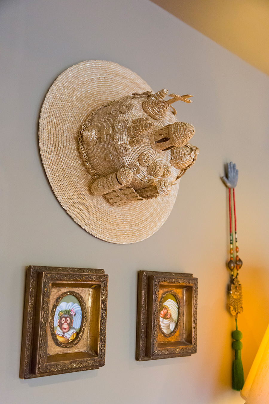 ヨーロッパの街並みを思わせるデザインの帽子を壁に。額の絵はこれまた猿モチーフ!
