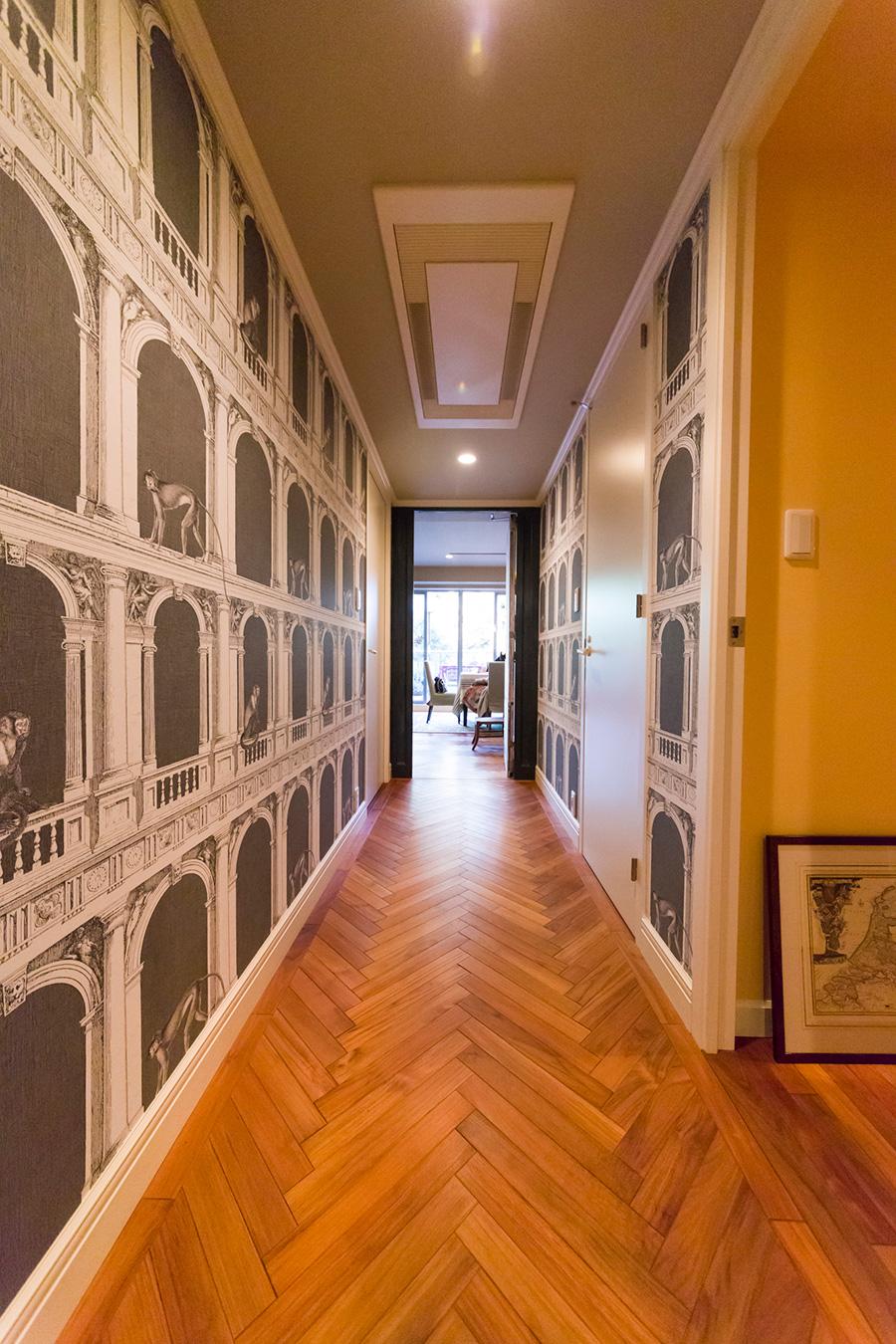 猿が遊ぶユニークな壁紙とヘリンボーンの床で、廊下が表情豊かな空間に。