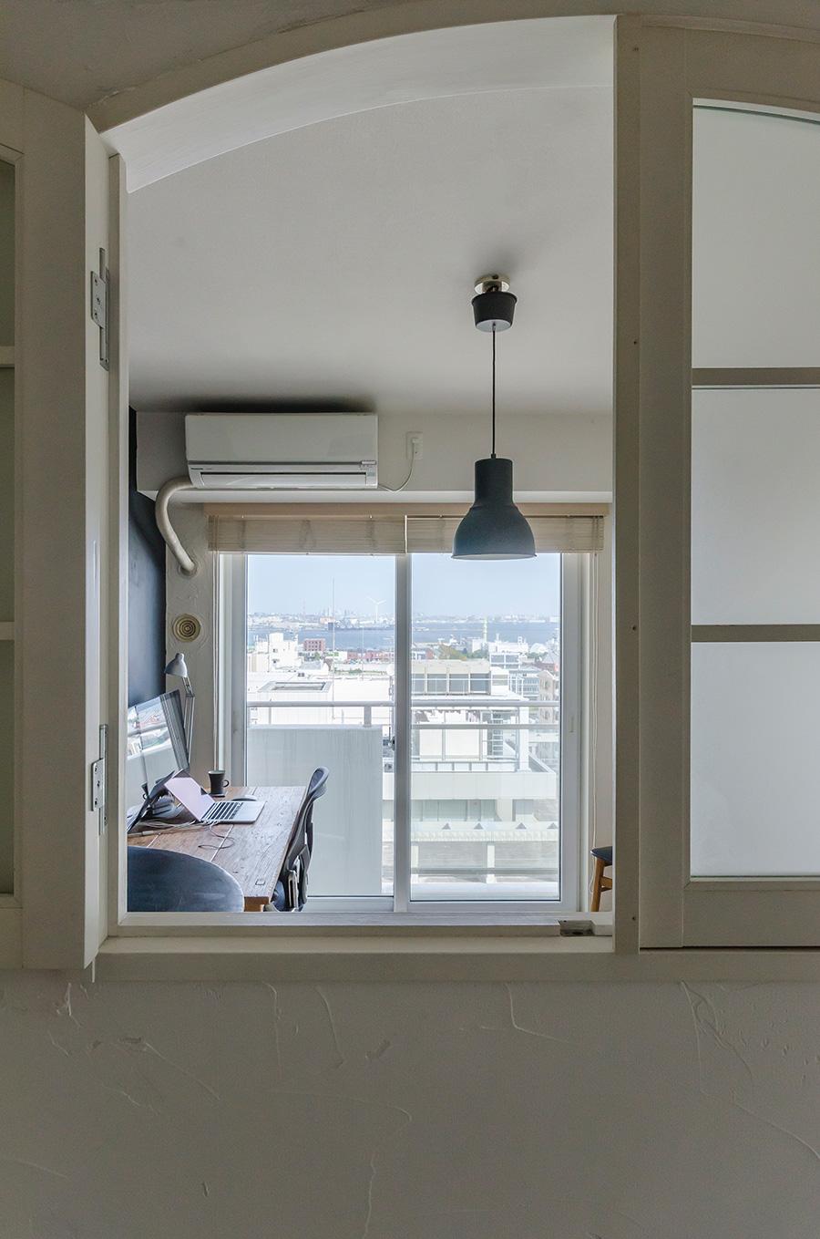 廊下と仕事部屋の間の壁にはアーチ型の小窓を設けた。ベランダからの光が通り抜ける。