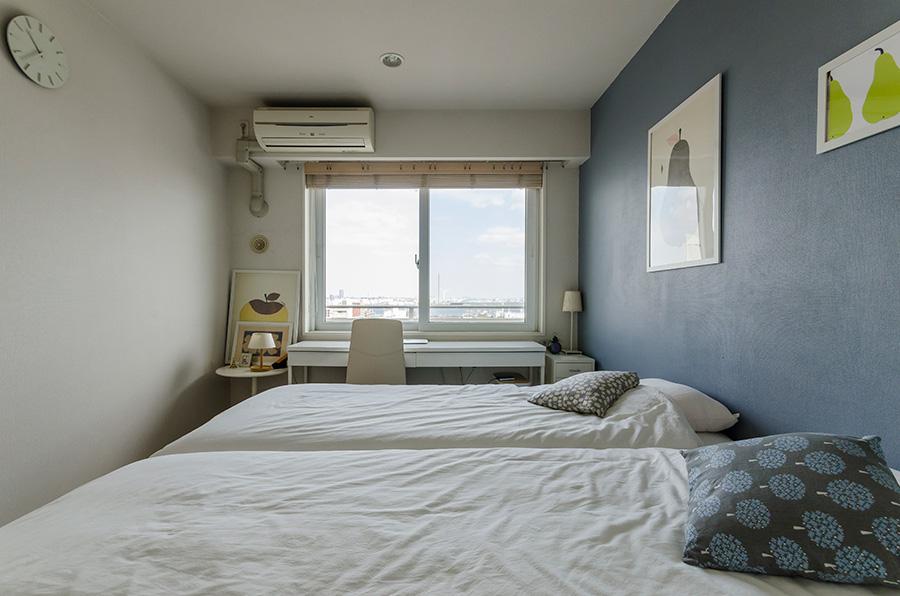 ブルーグレーに塗装した面に、お気に入りのポスターを飾るベッドルーム。窓際は妻の仕事用デスク。