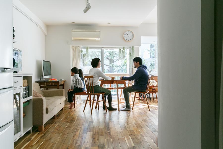 左の壁に沿うようにキッチンとソファが並び、南に面した窓の前にダイニングテーブルを配置している。