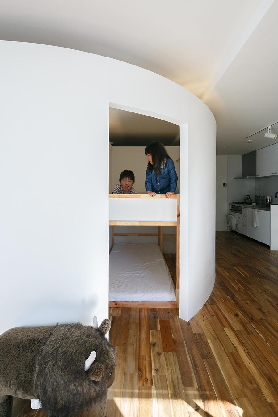 窓際からLDKを見通す。子ども用のスペースの2段ベッドから顔を出すきょうだい。ベッドは購入前に計測し、ピッタリと収まるように設計してもらった。