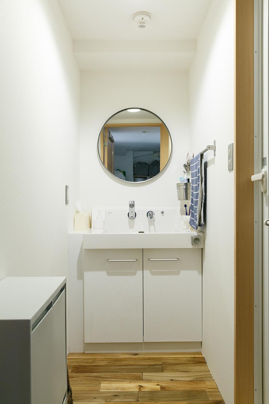 リノベーションでミラーだけ付けかえたという洗面所。洗面台は既存のものを使うことでコストダウンをはかった。